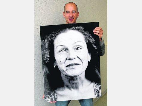 Der Diepholzer Künstler Jonathan Olbert mit einem der elf großen Portraits von blinden und sehbehinderten Menschen, die er ab Dienstag in der Mediothek zeigt. ·