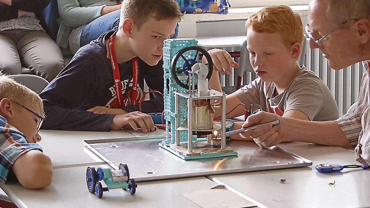 Yannik, Alex und Frode (von links) von der IGS Oyten beobachten interessiert das Erhitzen des Schwungrades ihres Modells.