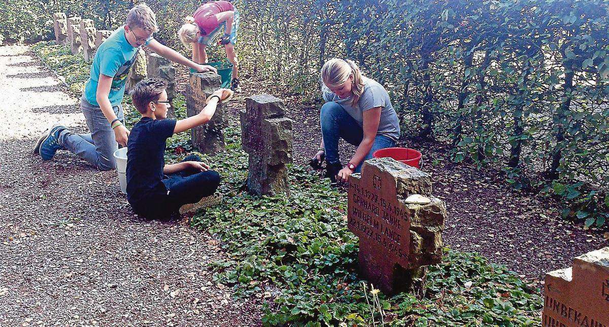 Georg Heise, Joshua Moritz, Emelie Rosebrock-Heemsoth und Kyra Klaft (von links) bringen die Kriegsgräber in Hohenaverbergen auf Vordermann. Die Arbeit war Teil eines groß angelegten Konfirmandenprojekts rund um den Volkstrauertag.
