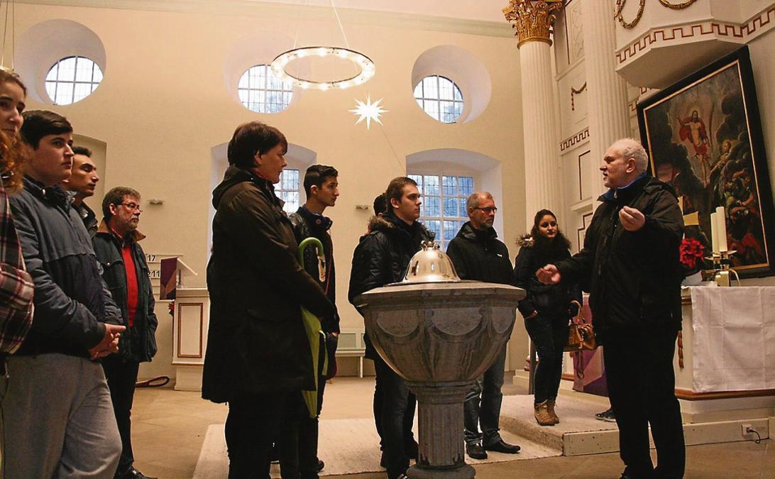 Schüler der Sprachlernklasse des Berufsbildungszentrum mit Lehrerinnen und externen Betreuern zu Gast in der St.-Nicolai-Kirche: Pastor Lutz Korn (rechts) informierte die jesidischen und muslimischen Flüchtlinge über christliche Symbole.