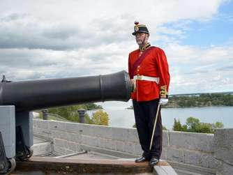 """Leftenant Colonel"" Mark Bennett steht neben einer Kanone in Fort Henry am St.-Lawrence-Strom."
