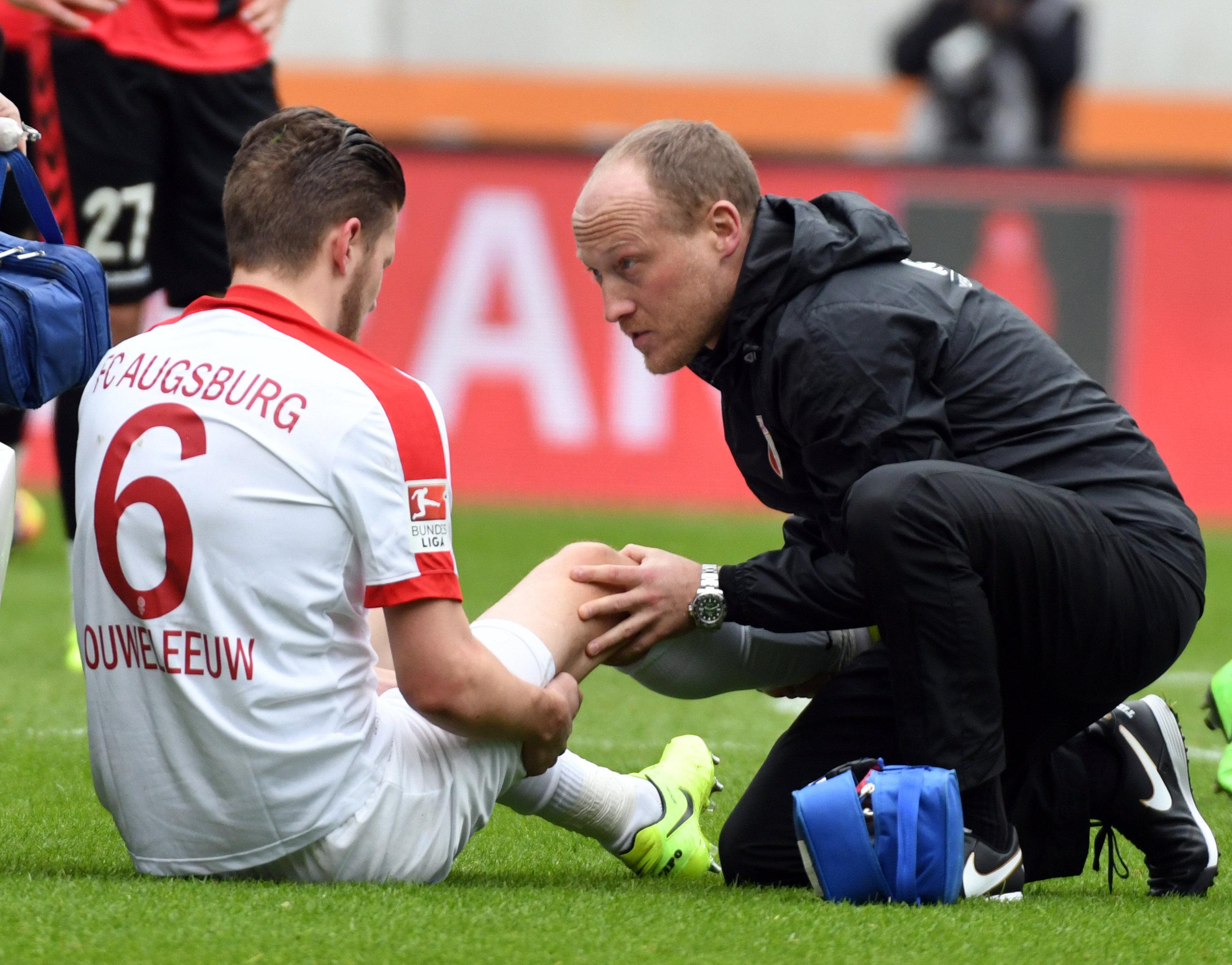 Der Moment, in dem die Auswechslung feststand: Jeffrey Gouweleeuw wird von Arzt Peter Stiller im Spiel gegen den FC Freiburg behandelt.