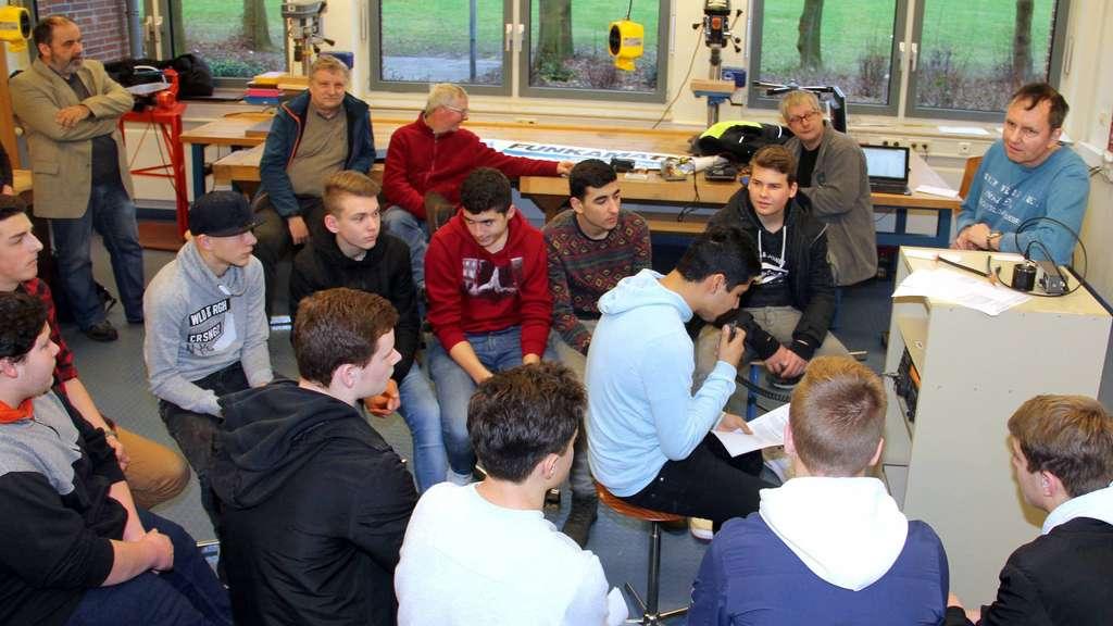 """Die Schüler der Amateurfunk-AG für Neuntklässler stellen den ersten Kontakt mit der gespendeten Funkanlage her – Andreas Richter (rechts) """"souffliert"""", wenn nötig. - Foto: Behling"""