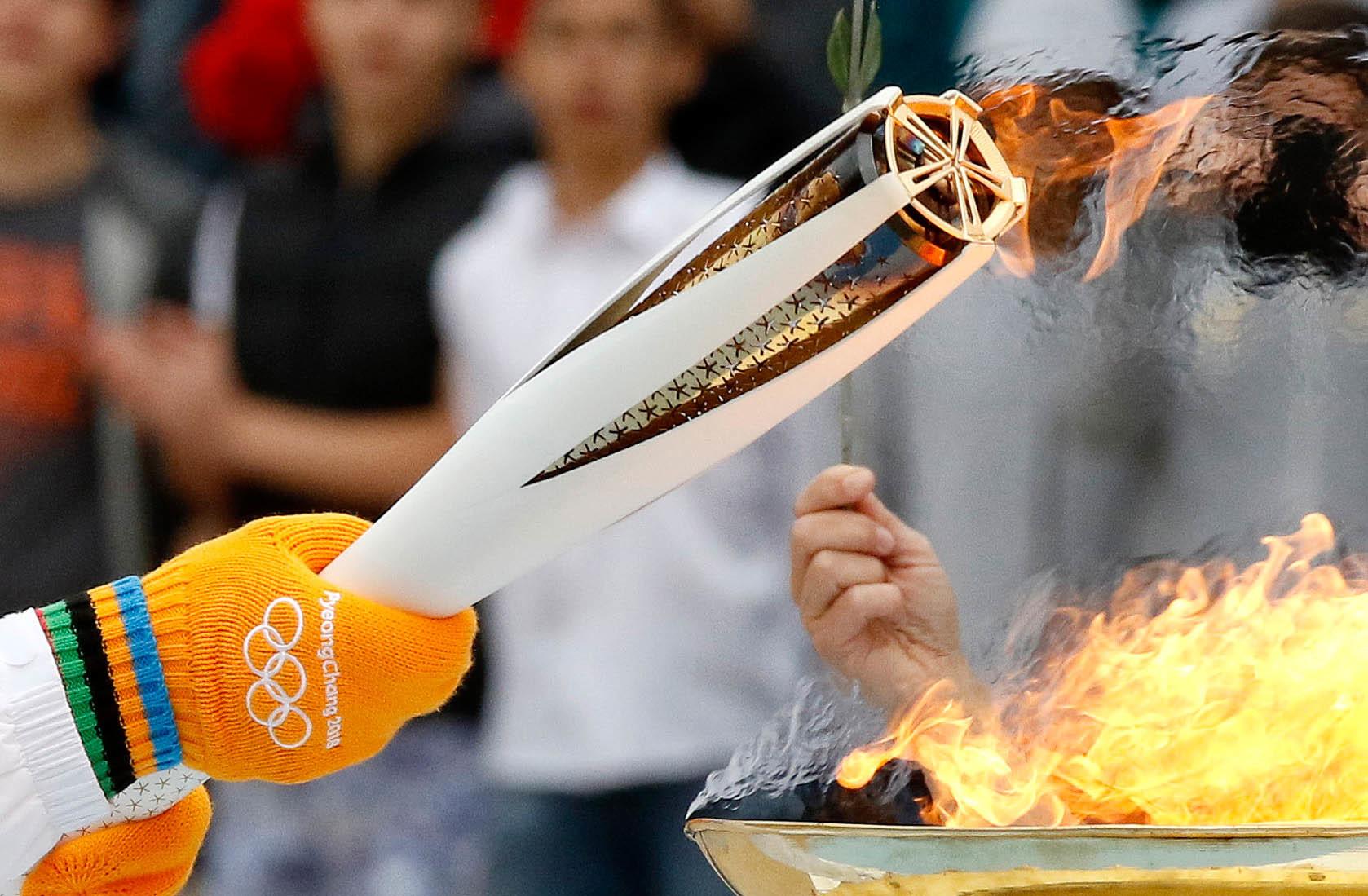 Die Olympische Fackel wird übergeben.