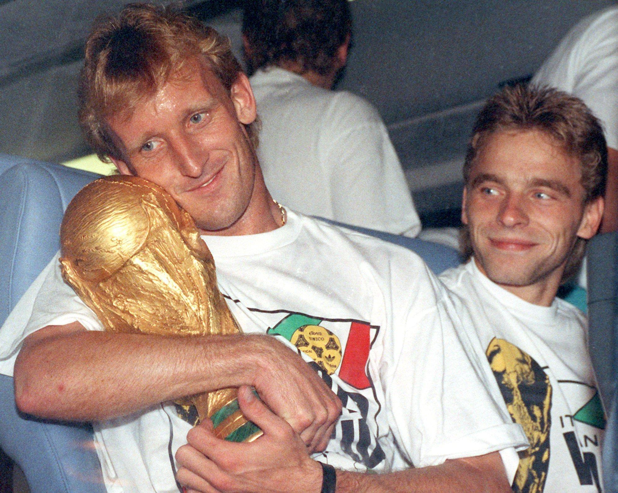 Andy Brehme (l.) kuschelt mit dem WM-Pokal: Jetzt verkauft er zwei Souvenirs vom Turnier 1990 in Italien.