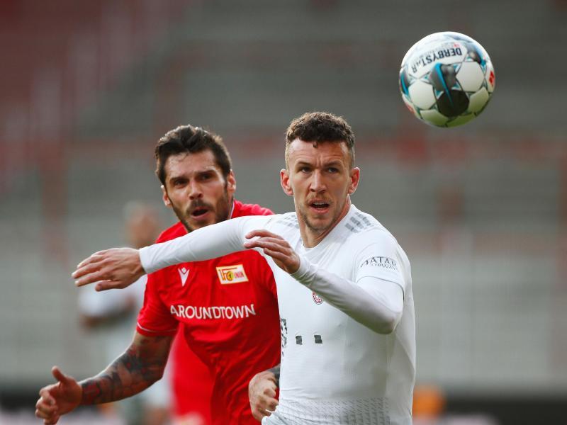 Bayern Münchens Ivan Perisic (r) im Zweikampf mit Unions Christopher Trimmel. Foto: Hannibal Hanschke/Reuters-Pool/dpa