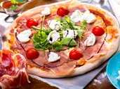 close up of delicious italian pizza with ham, mozzarella, tomatoes and arugula (sebasnoo)