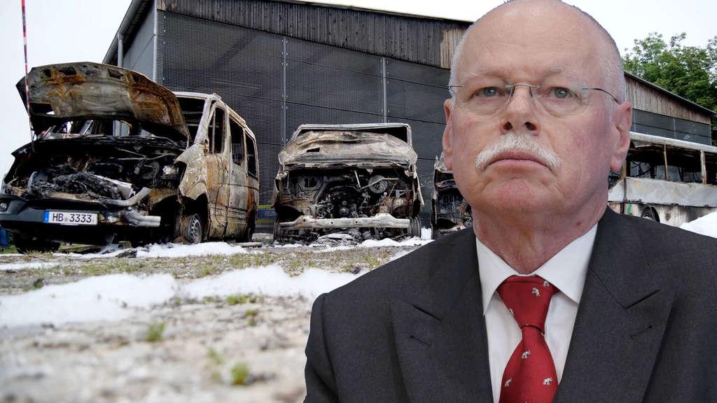 Drei ausgebrannte Gruppenwagen und ein ausgebrannter Bus der Bereitschaftspolizei Bremen stehen vor einer Halle. Davor montiert Innenminister Ulrich Mäurer.