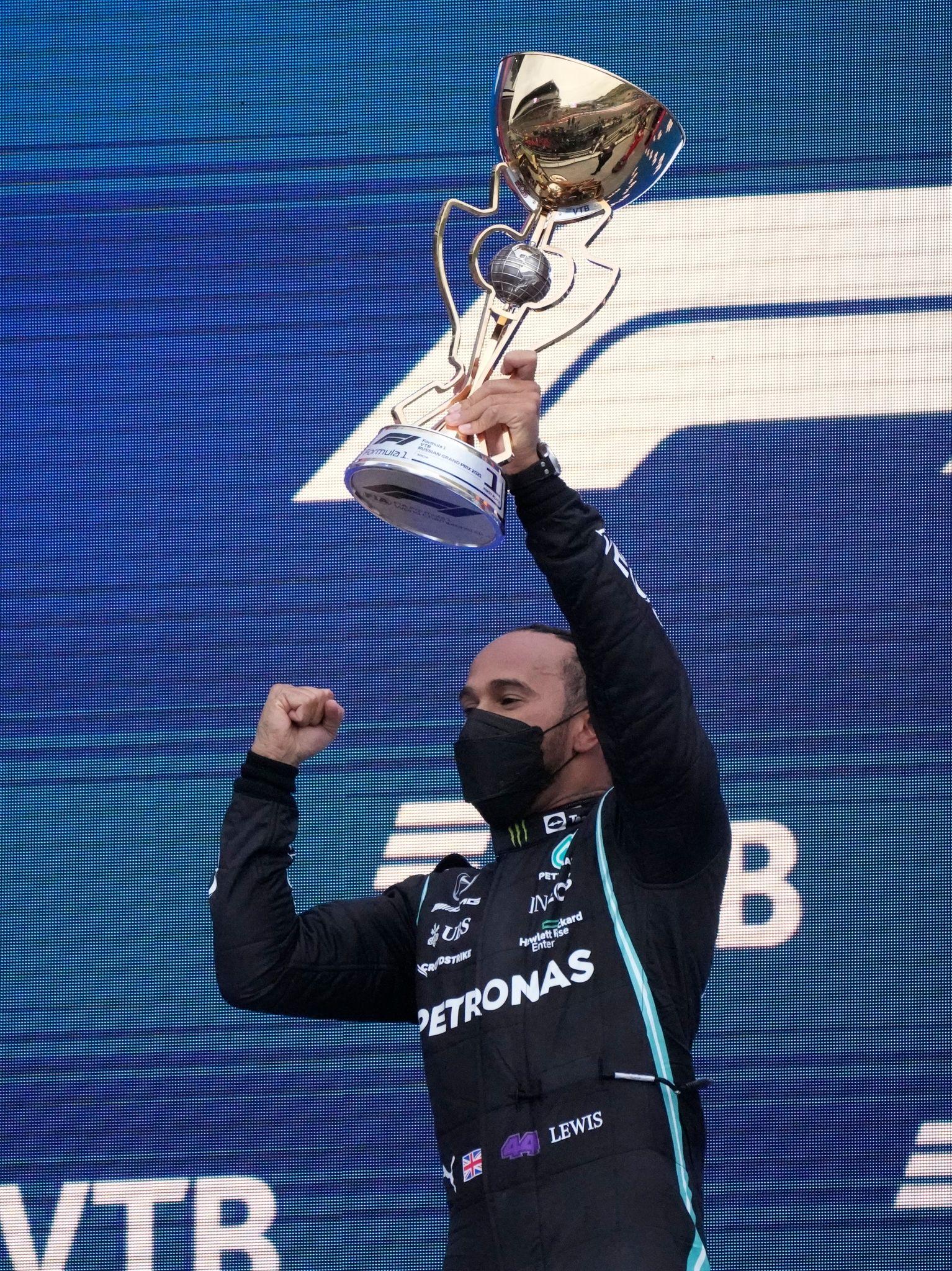 Weltmeister Lewis Hamilton mit der Siegertrophäe.
